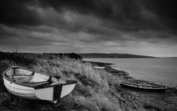 Old decayed rowing boats on shore of lake with stormy sky overhe Royalty Free Stock Images