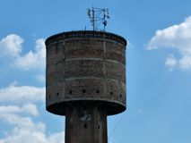 Old decaying brick tower functioning as radio tower. Old decaying decommissioned brick water tower building functioning as radio and cell tower under blue sky royalty free stock images