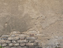 Old decaying brick wall. Background texture of peeled plaster. Stock Photos