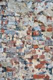 Old decaying brick wall with repairs and crumbling cement layer. Old irregular ecaying brick wall with repairs and crumbling cement layer Stock Images