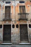 Old decaying italian architecture in brown tones. Old windows and doors and decaying cracking terracotta brown plaster balconies with dark railings not shutters stock photo
