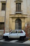 Old decaying italian architecture in yellow tones with old white car parked in front. Old windows and doors and decaying cracking terracotta yellow plaster stock photos