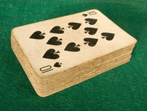 Old deck of cards on a green baize poker table. Royalty Free Stock Images