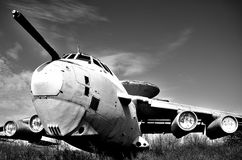 The dismissed worker. The old decommissioned plane is waiting for its fate to be sawn in the landfill illuminated by the bright sun. Black and white photo Royalty Free Stock Photos