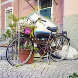 Old decorated bike. Color image. Old lady's bike, decorated with flowers and various objects, positioned as urban decoration in a small fishermen village on the stock photo
