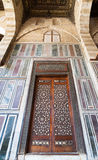 Old decorated marble wall with a historic ornate wooden door Royalty Free Stock Images
