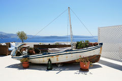 Old Decorative Boat. Old fishing boat as a decoration of the hotel terrace with the view at caldera of the Santorini island in Greece Royalty Free Stock Photography