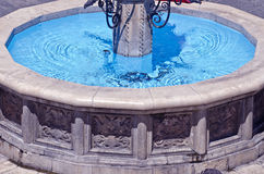 Old decorative city Fountain with blue water Royalty Free Stock Photography