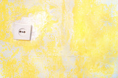 Old decrepit wall with electrical socket. Wall socket on the yellow old plastered wall whith copyspace. Old electrical outlet on a decrepit wall. Fragment of a Royalty Free Stock Photo