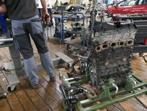 An old, defective car engine is replaced Stock Image