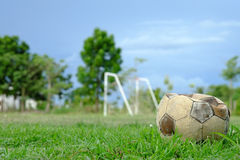 Old deflated soccer ball, old deflated football on the green grass Stock Photography