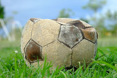 Old deflated soccer ball, old deflated football on the green grass Stock Image