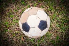 Old deflated soccer ball, old deflated football Stock Photo