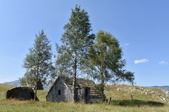 The old, delapidated abandoned shepherds traditionally built wooden huts Stock Image