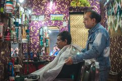 How is that look?. Old Delhi, India : February 15th, 2015 - A shot of a barber preparing his customer for a hair cut Stock Photos