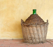Old demijohn aka carboy for wine, wicker straw basket. by house. Y. Old wine. Actual or metaphor time passing, age Royalty Free Stock Image