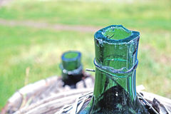 Old demijohn glass wrapped in wicker. Old demijohn glass wrapped in wicker abandoned Stock Photos