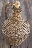 Old demijohn wicker wrapped glass bottle on  wooden table. Old demijohn wicker wrapped glass bottle on old  wooden table Royalty Free Stock Images
