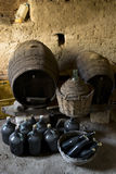 Old demijohns aged wine bottles and wooden barrels in a basement Royalty Free Stock Images
