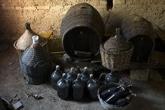 Old demijohns aged wine bottles and wooden barrels in a basement Stock Images
