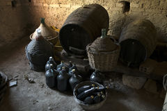Old demijohns aged wine bottles and wooden barrels in a basement Royalty Free Stock Photo