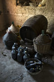 Old demijohns aged wine bottles and wooden barrels in a basement Royalty Free Stock Photos