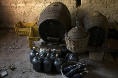 Old demijohns aged wine bottles and wooden barrels in a basement Royalty Free Stock Photography
