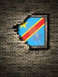 Old Democratic Republic of Congo flag in brick wall. 3d rendering of a Democratic Republic of Congo flag over a rusty metallic plate embedded on an old brick Stock Image