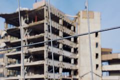 Old demolition building unfocused with consruction site fence in focus. Old half destroyed building which will be demolished against blue cloudless sky unfocused royalty free stock image