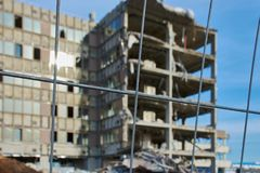 Old demolition building unfocused with construction site fence in focus. Old half destroyed building which will be demolished against blue cloudless sky stock photo