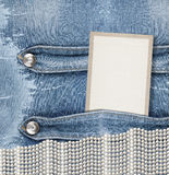 Old denim background with paper frame. And luxury pearls Royalty Free Stock Image