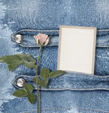 Old denim background with paper frame. And pink roses Royalty Free Stock Photography