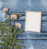 Old denim background with paper frame. And pink roses Stock Image