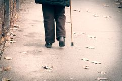 Old depressed woman walk alone down the street with walking stick or cane feeling lonely and lost view from back.  stock photography