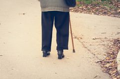 Old depressed woman walk alone down the street with walking stick or cane feeling lonely and lost view from back