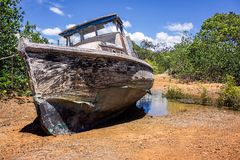 Old derelict boat in mangroves. Old, weathered and damaged wooden boat abandoned on a small beach in the mangroves at Sarina, Queensland, Australia stock photo
