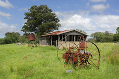 Old derelict farm shed and rusty cart wheels at Benandarah. Old farm shed or barn, with a rusty water tank and cart wheels lie in overgrown grass in Benandarah Royalty Free Stock Image
