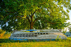 Old derelict wooden boat under a tree. HDR picture. Old wooden boat needs repair. lying under a tree in green gras. picture taken in HDR Stock Photo