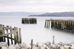 Old derelict wooden jetty pier in sea coast town of Helensburgh Argyll. Uk royalty free stock images