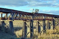 Old derelict wooden railroad bridge in countryside stock image