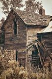 Old Deserted House. A old abandoned house on a gravel road. Done in sepia royalty free stock image