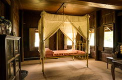 Old designed bed. The very old designed bed made from golden metal iron just for the very rich people in teak house Stock Photo