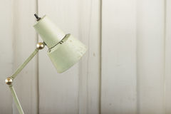Old desk lamp on wood wall Stock Images