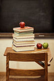 Old desk with a stack of books with vintage look. Old desk with a stack of books and apple with vintage look Royalty Free Stock Image