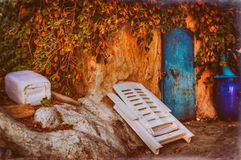 Old Desolated Storage. An old desolated storage with portable chair, plastic can and barrel. Surrounded with ivy type of plant on top. Entire structure looks royalty free stock image