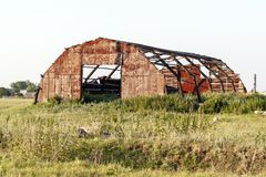 The destroyed metal hangar in the countryside. stock image