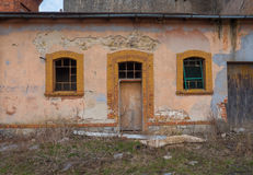 Old, destroyed building with door and two windows. Old, destroyed building with door and two windows Stock Photo