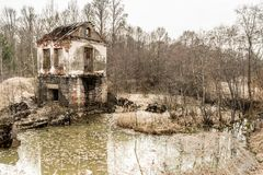 Old destroyed building of the hydroelectric plant with moss-grown walls is located in a forest surrounded by dry grass and shrubs royalty free stock photography