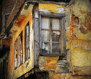 Old destroyed house. Part of the old ruined house with broken windows and damaged walls, after the natural disaster Royalty Free Stock Image