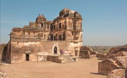 Old destroyed palace with brick towers and some indian women in sari, India. stock photos